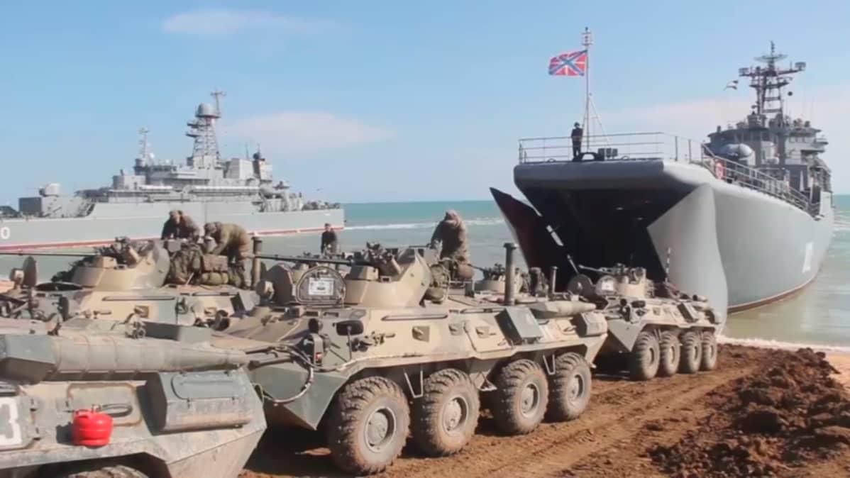 Kolme panssariajoneuvoa on merenrannalla. Rannassa on maihinnousualus, jonka keula on avattu. Panssariajoneuvojen päällä työskentelee sotilaita. Aluksen keulassa laivaston lipun vieressä seisoo merisotilas.