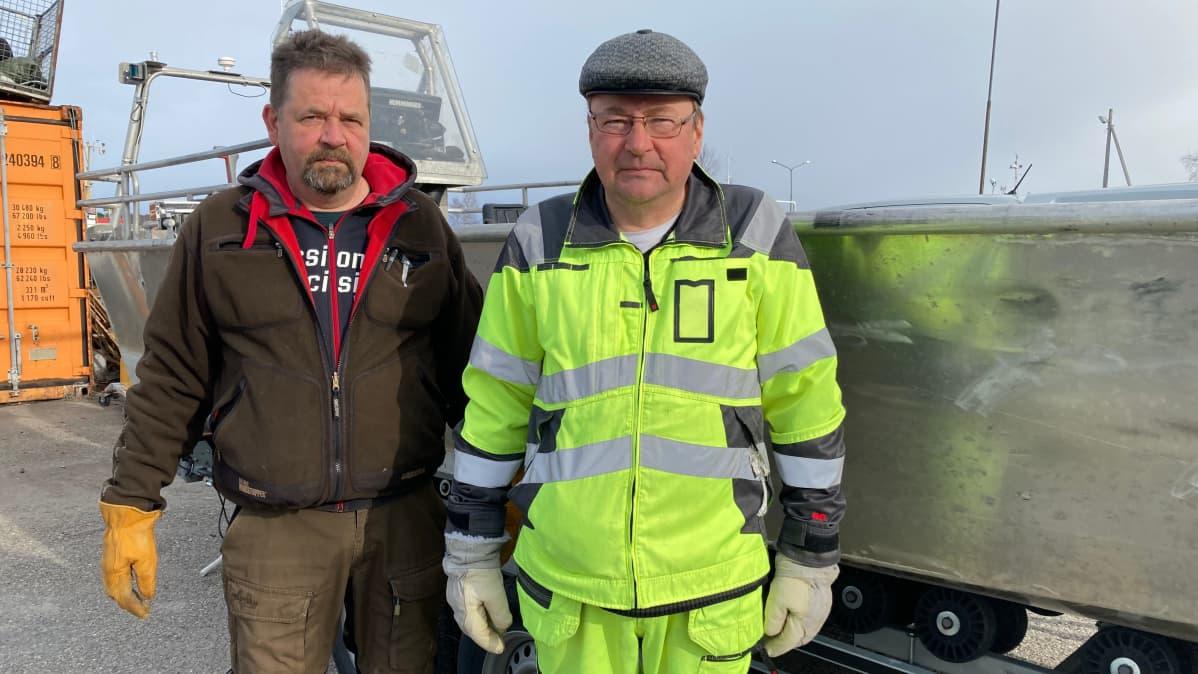 Jouni ja Kari Heinikoski seisovat telakalla olevan kalastusveneen edessä. Miehet eivät hymyile.