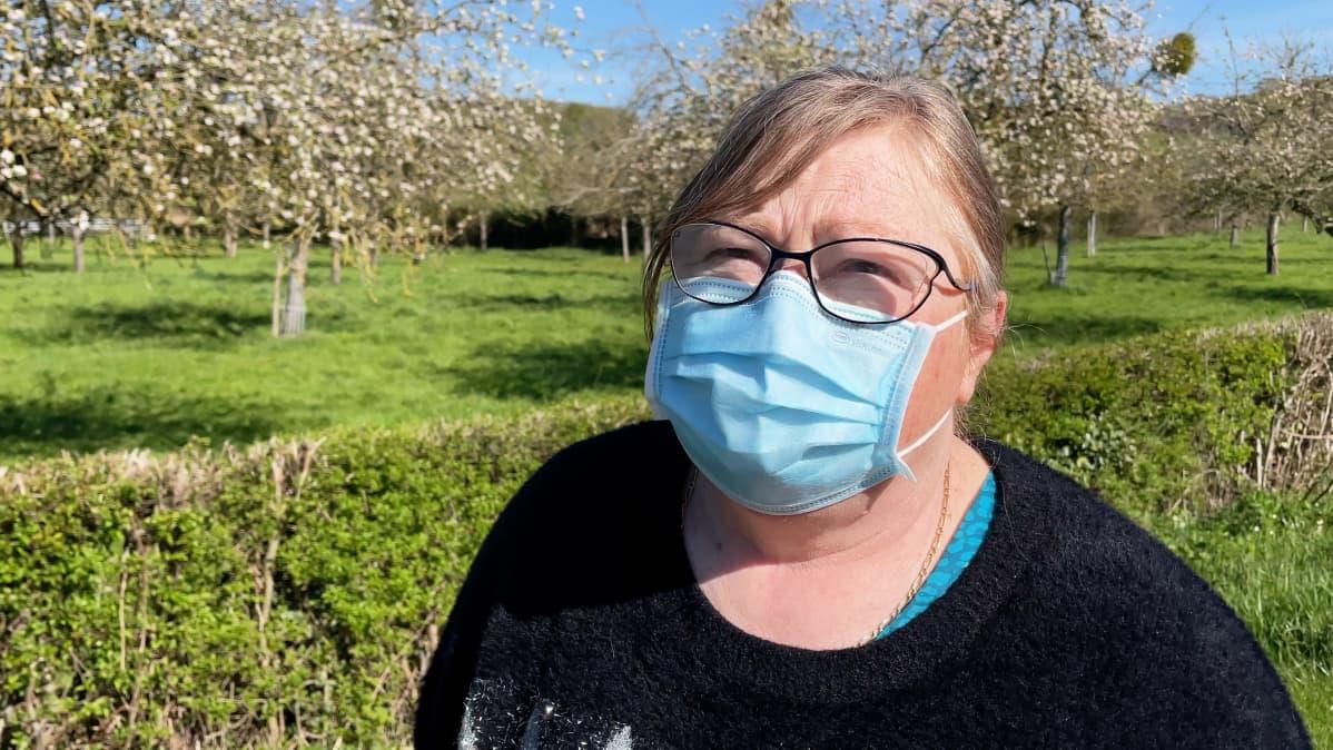 Nainen maski kasvoillaan, taustalla omenapuita