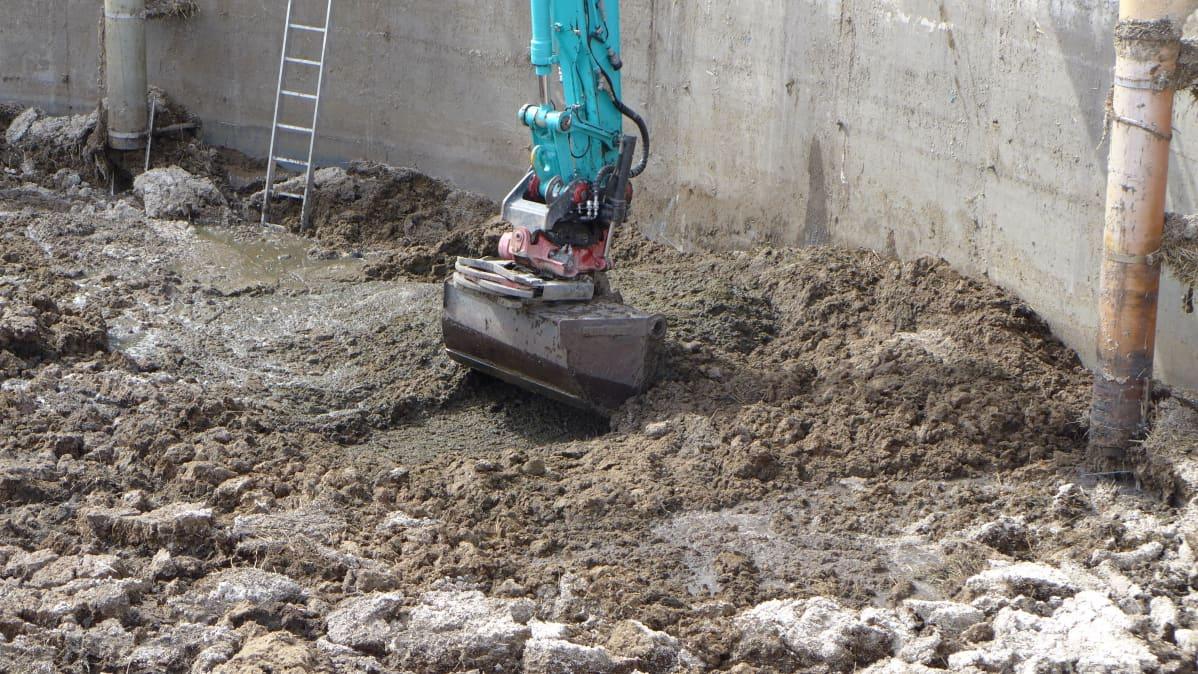 Kaivurin kauha kaivaa lantakasaa