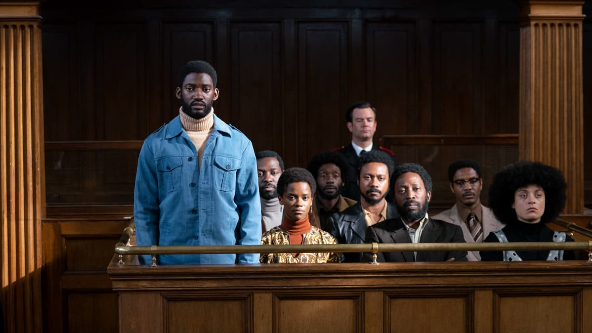 Sinitakkinen musta mies seisoo oikeussalissa.