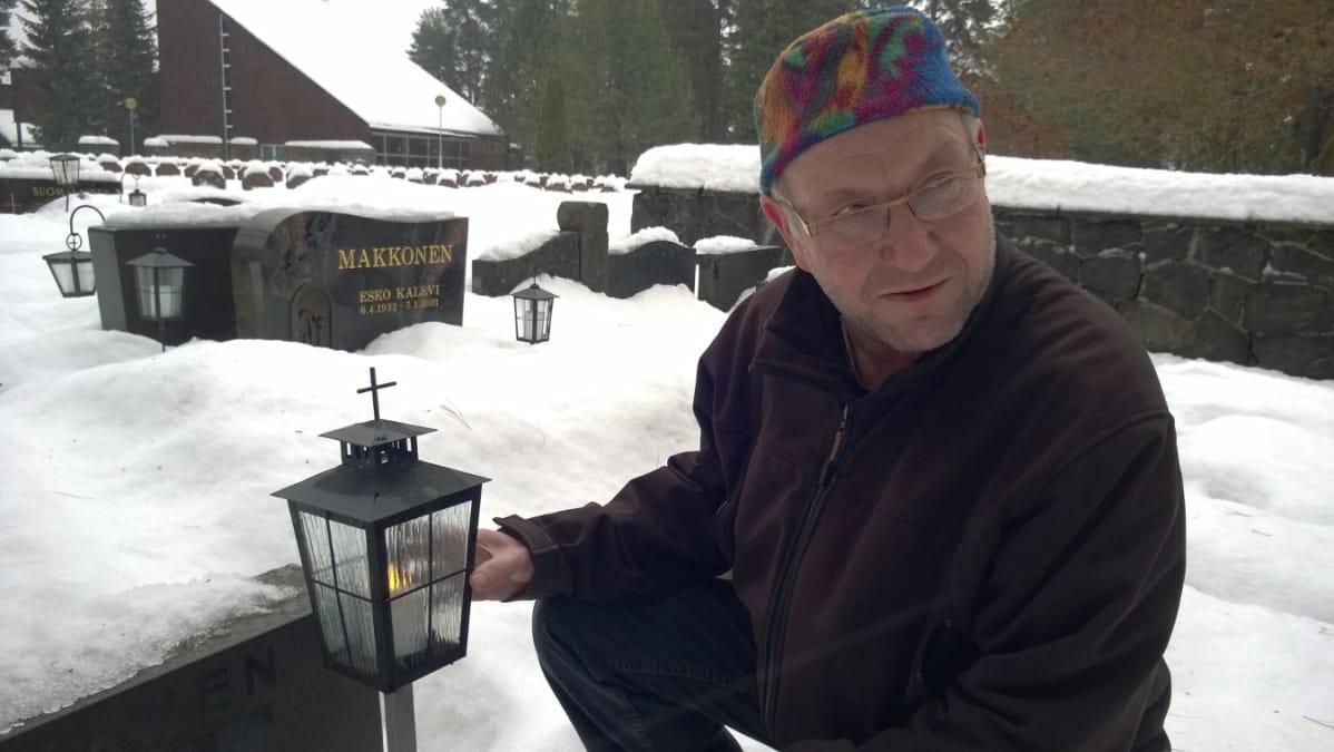 Savonlinnan seurakunnan ylipuutarhuri Pasi Inkinen esittelee led-kynttilää  Talvisalon hautausmaalla joulukuussa 2017. 7998b8c19d