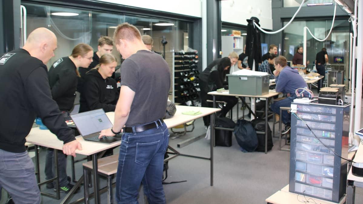 Opiskelijoita pöydän äärelle
