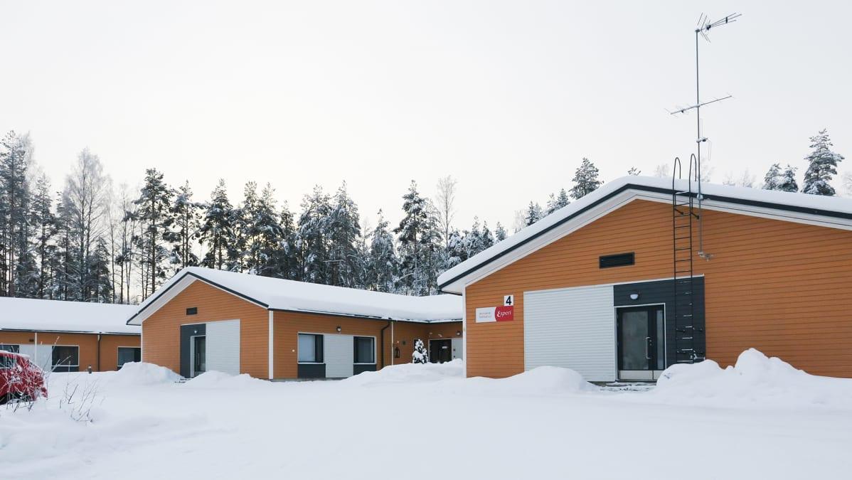 Kolme oranssiksi maalattua hoivakotirakennusta rinnan lumisella pihalla.