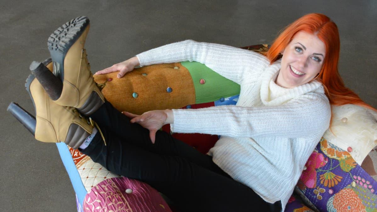 Punatukkainen nainen istuu ja hulluttelee värikkäässä nojatuolissa