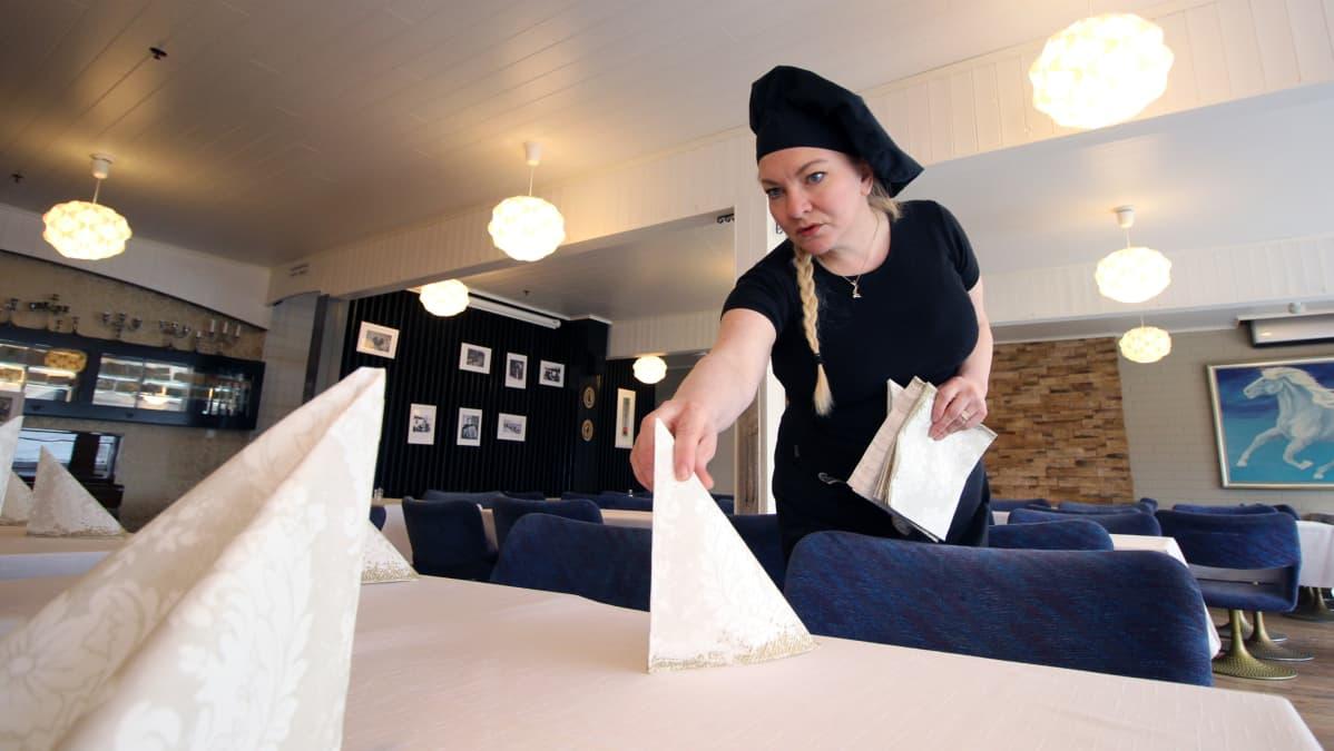 Orilammen lomakeskuksen yrittäjä Helena Topan asettelee serviettejä pöytään.