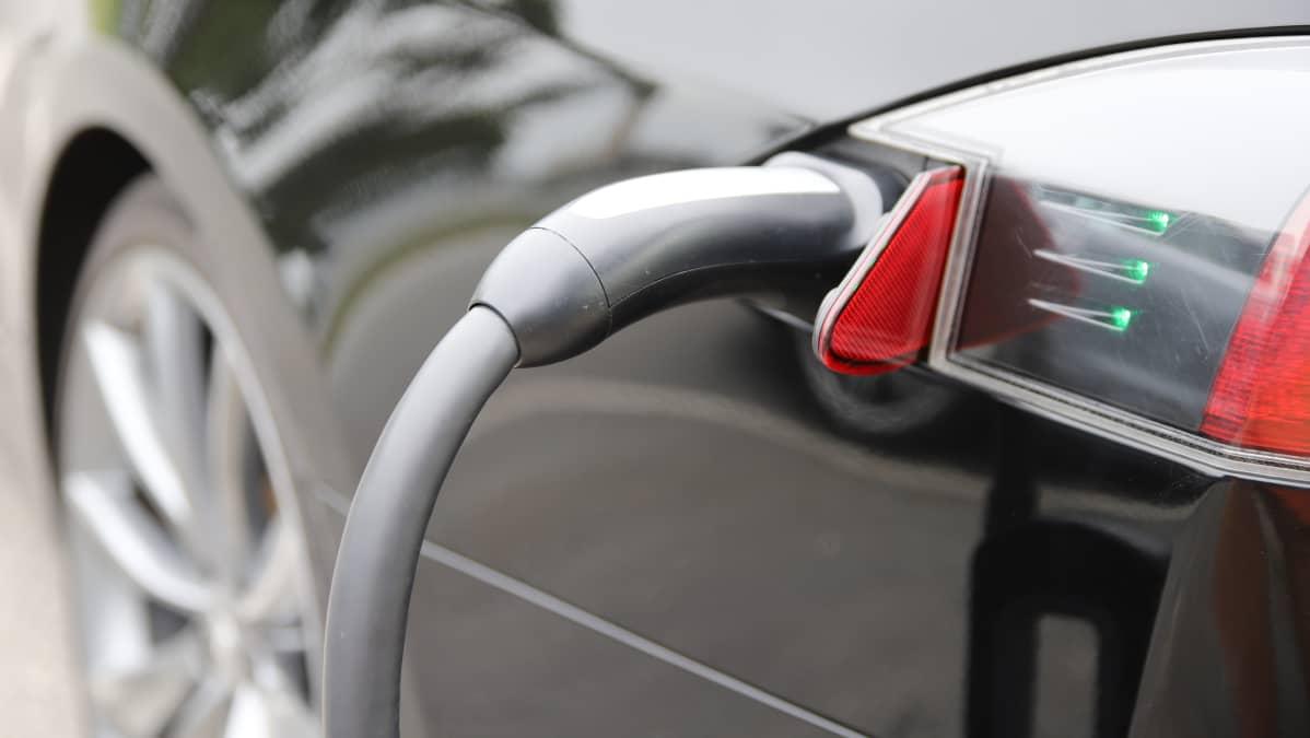 Sähköauto ja latausjohto. Sähköautojen latauspaikkoja löytyy myös kauppakeskuksista, joissa lataamisen voi hoitaa vaikka kauppareissun aikana.