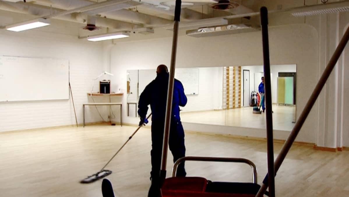 Siivoja moppaa lattioita yrityksen tiloissa.