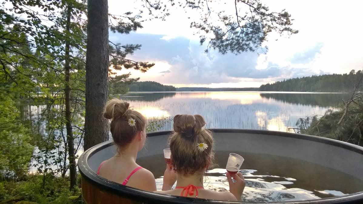 Kaksi naista kylpypaljussa järvenrannassa