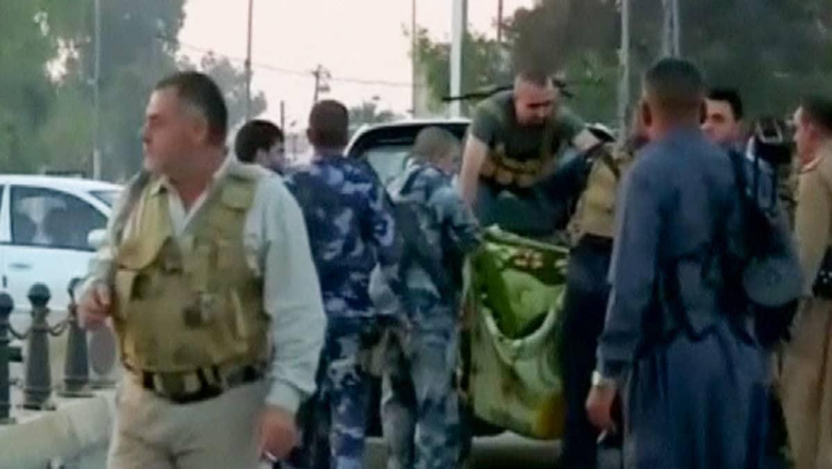 Paikalliset viranomaiset nostivat iskun tekijän ruumista autoon Kirkukissa 21. lokakuuta 2016.