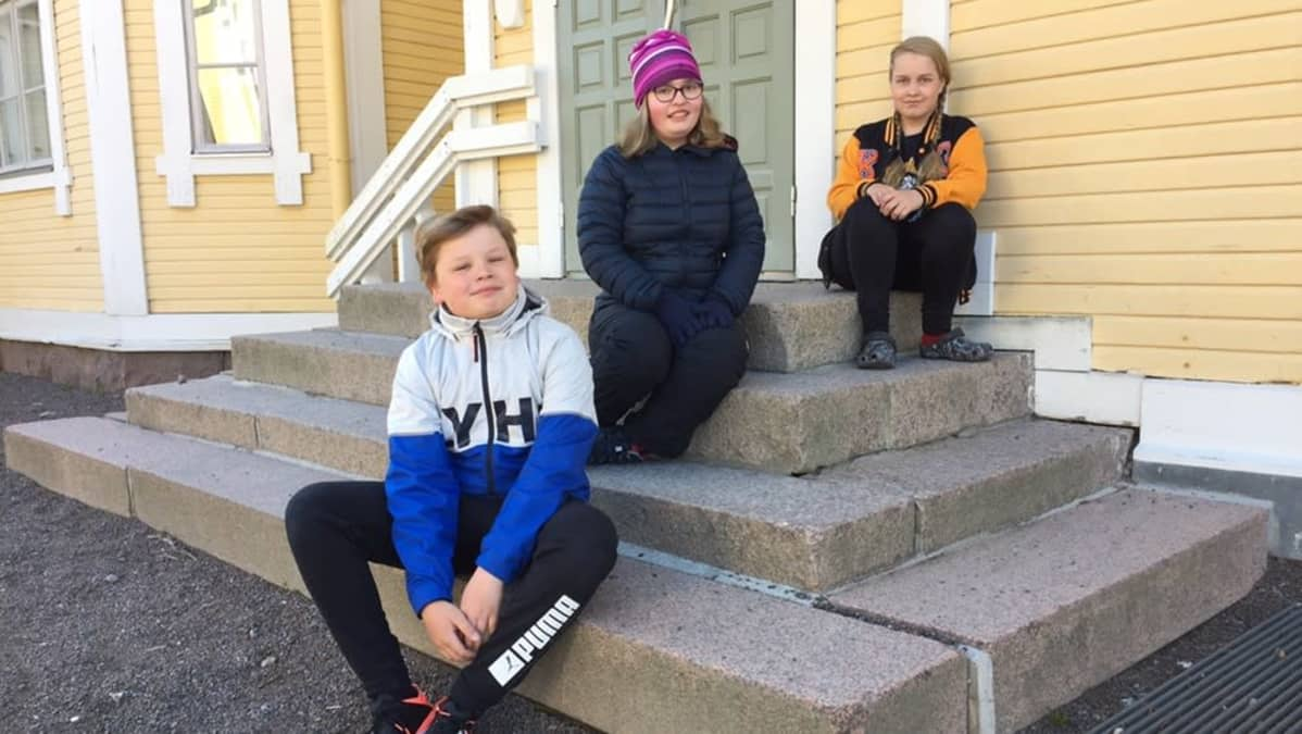 Lappeenrannan Lönnrotin koulun 6.-luokkalaiset Julius, Aino ja Liia istuvat ulkoportailla.