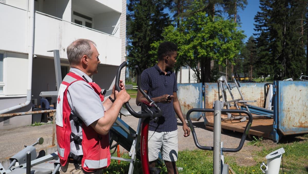 Paiholan vastaanottokeskuksen johtaja ja asukas lajittelevat kierrätettävää tavaraa
