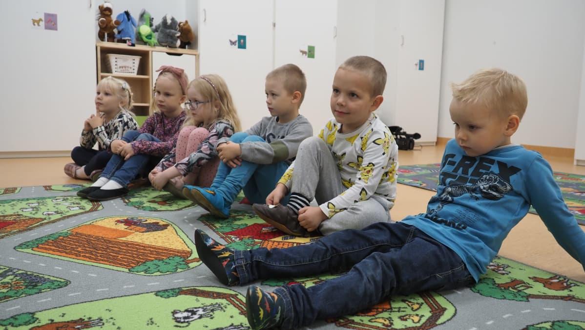 Alle kouluikäisiä lapsia istuu vierekkäin päiväkodin lattialla värikkäällä matolla.