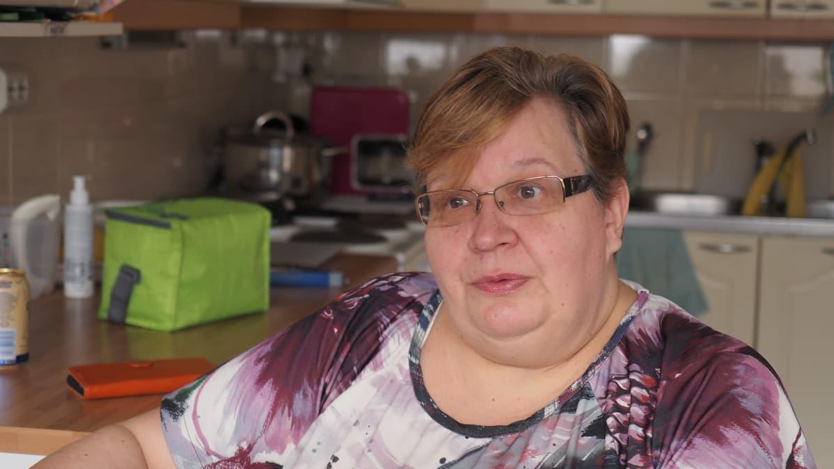 Nainen keittiönpöydän ääressä