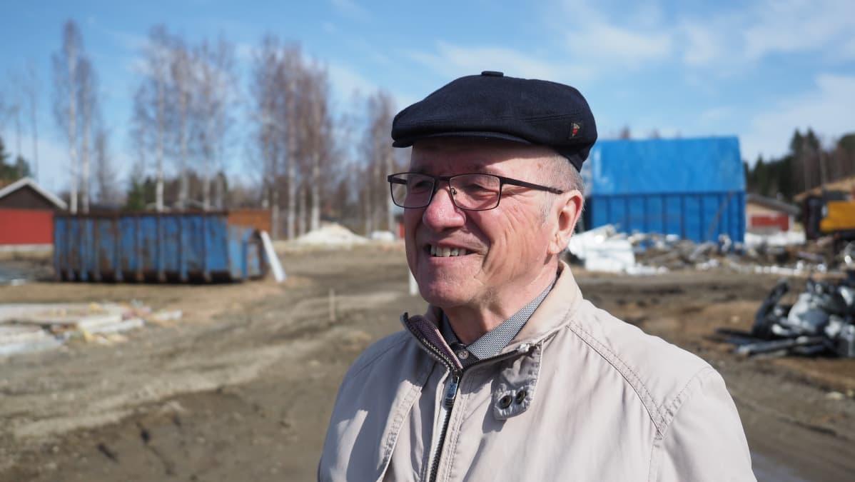 Polvijärven entinen kunnanjohtaja Pauli Vaittinen seisoo vuokrataloyhtiön purkutyömaalla.