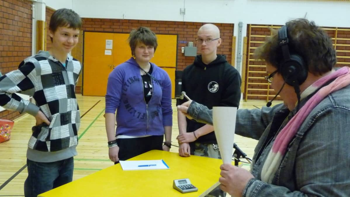 Juontaja Satu Haapanen käynnistää sananselityksen ajan Pertunmaan joukkueelle. Joukkueessa Perttu Ratilainen, Leena Ahtiainen ja Pentti Laitinen.