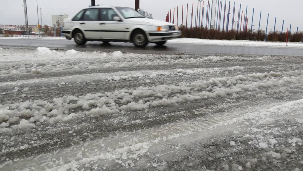 Talvinen luminen tie Kemissä, valkoinen Volvo ajaa kiertoliittymässä.
