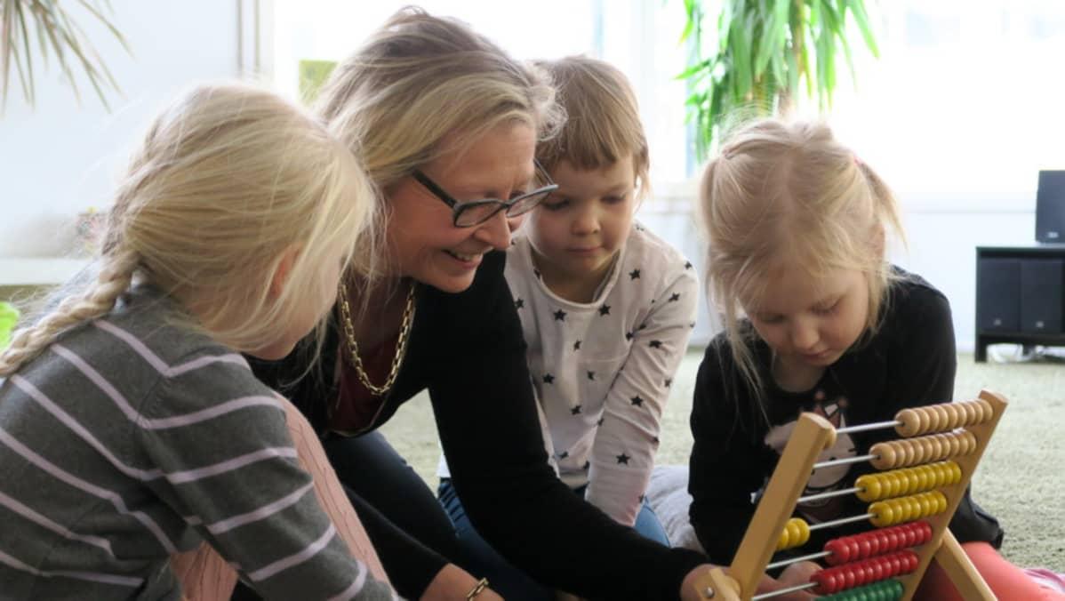 Sari Louhio-Järvinen leikkii kolmen tytön kanssa helmitaululla