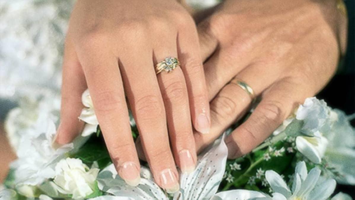 Vihkisormukset naisen ja miehen sormissa.