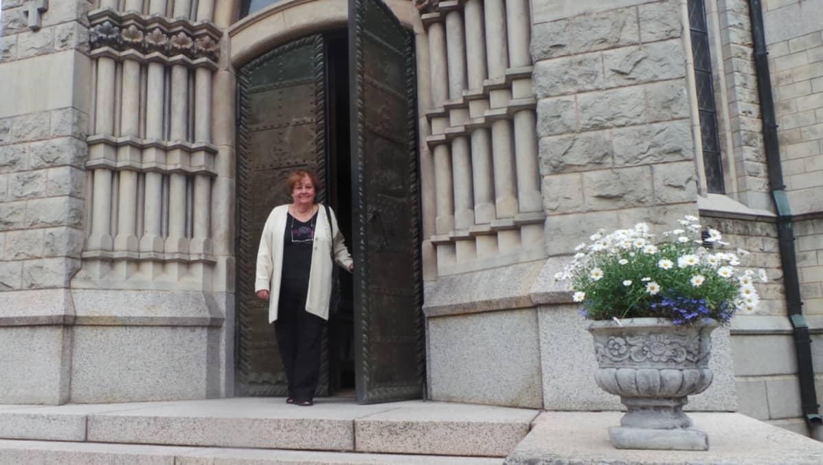 Nainen ovensuussa. Ovi on raskas teräsovi.