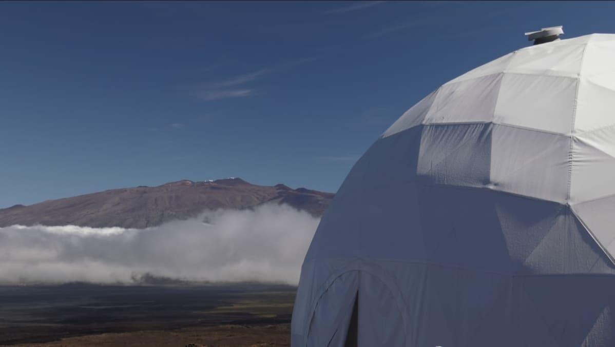Telttamainen kupu, jonka takana nousee vuorenhuippu pilvistä.