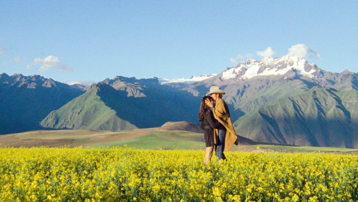 Maria (Stella Garcia) ja Kansas (Dennis Hopper) kukkivassa pellossa, taustalla mahtavia vuoria. Kuva elokuvasta The Last Movie
