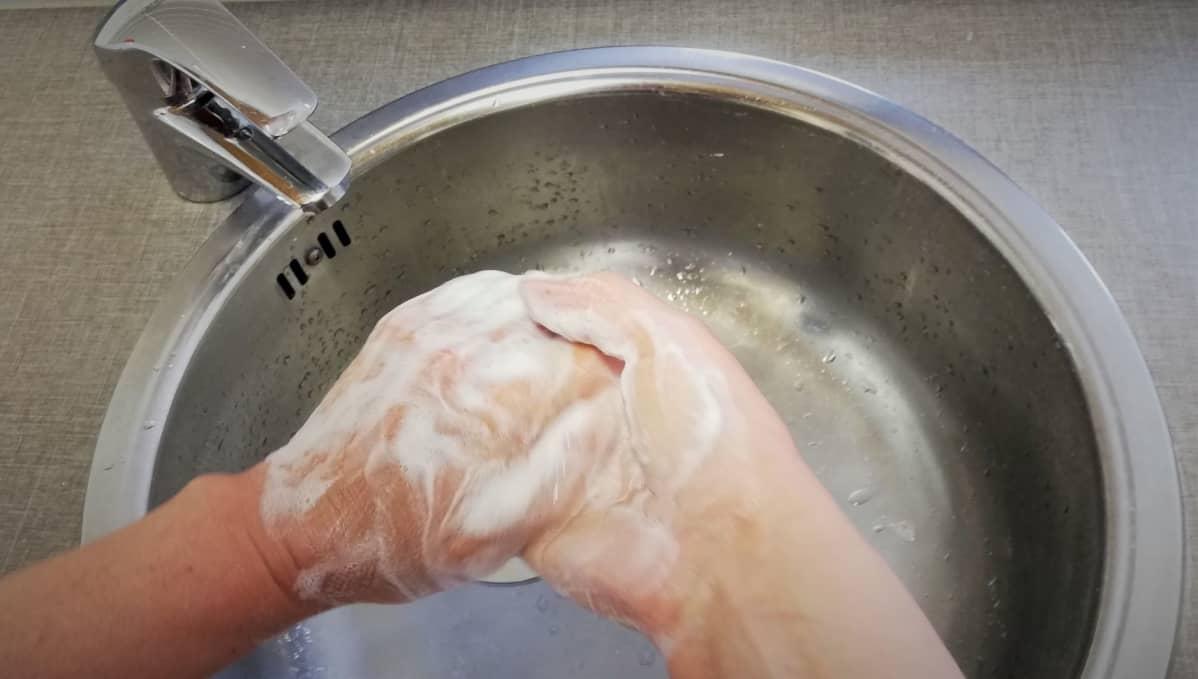 Nainen pesee käsiään.
