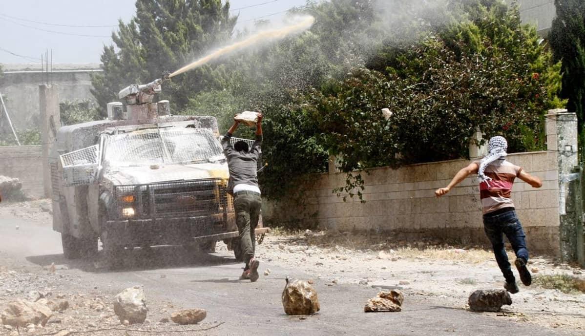 Palestiinalaismielenosoittajat heittivät kiviä kohti Israelin joukkojen vesitykkiä Qadomemissa. Kuva on toukokuulta 2015.