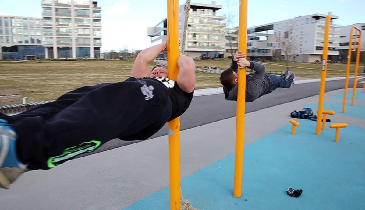 Kaksi miestä tekee shoulder flag -liikettä