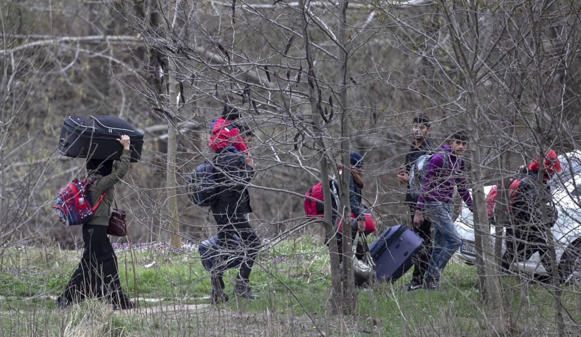 Viisi pakolaista kantaa laukkujaan metsän siimeksessä.