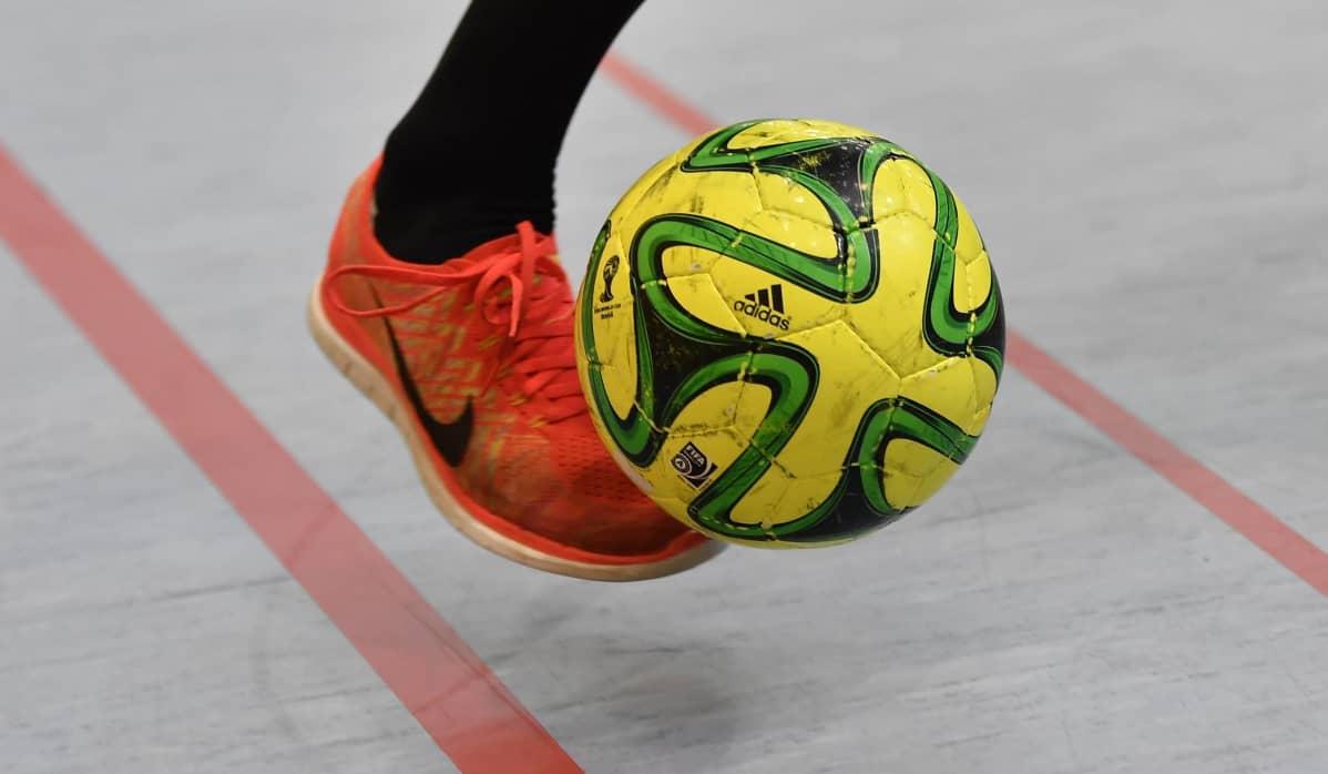 Person med orange gymnastisko sparkar gul futsalboll.