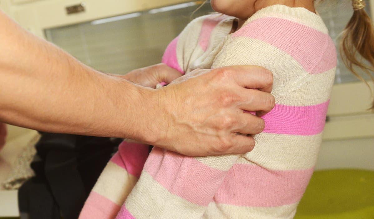 Lasta ravistetaan käsistä.
