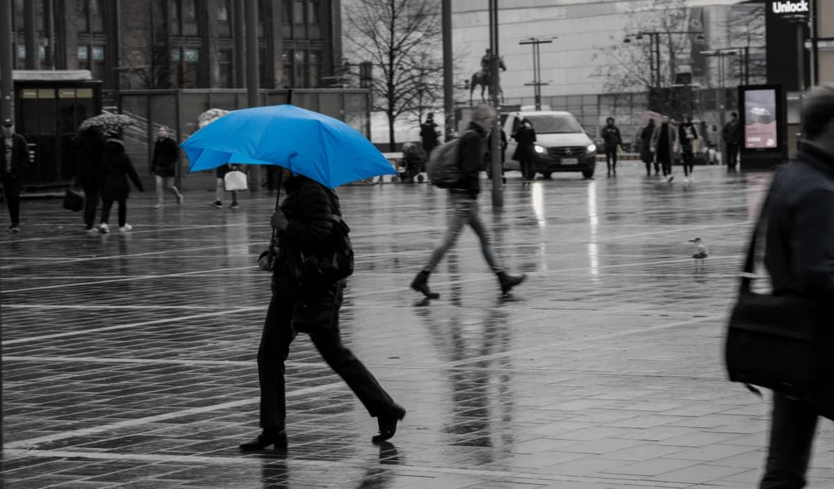 Nainen kävelee sateisessa säässä sinisen sateenvarjon alla.