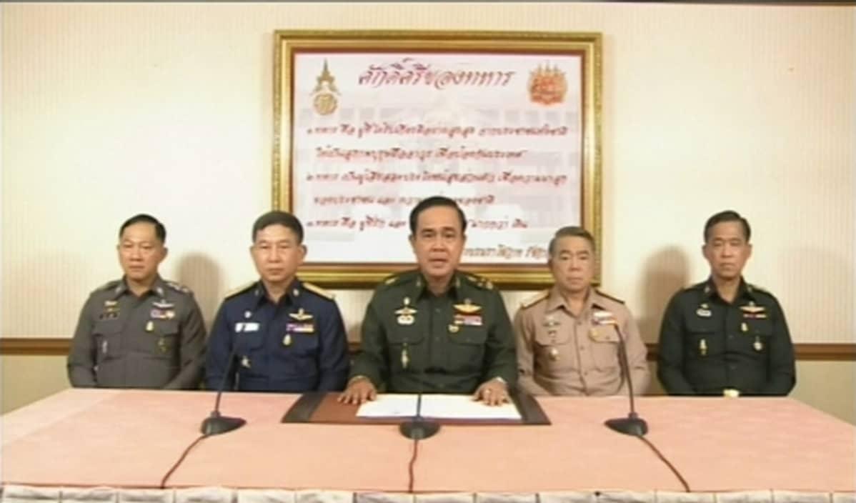 Kuvankaappaus televisioidusta tiedotustilasuudesta 22. toukokuuta. Kuvan keskellä puhuu Thaimaan armeijan päällikkö Prayuth Chan-ocha.