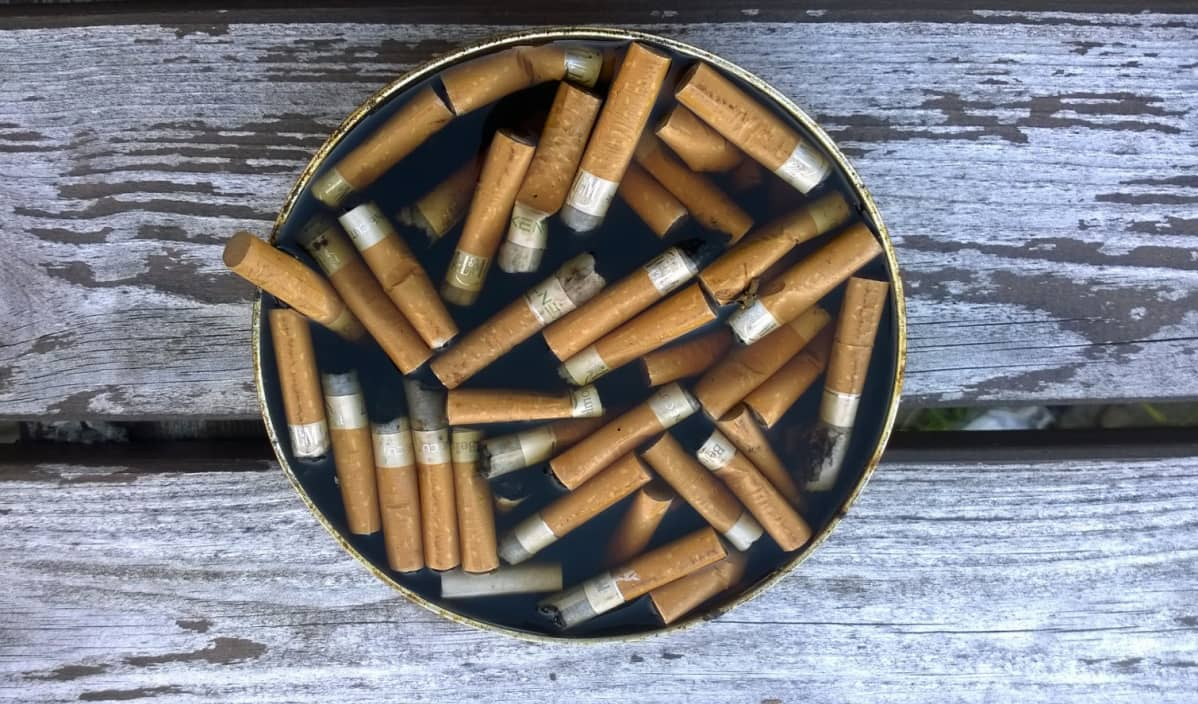 Veden täyttämä, tupakannatsoja täynnä oleva tuhkakuppi kuluneella puupöydällä.
