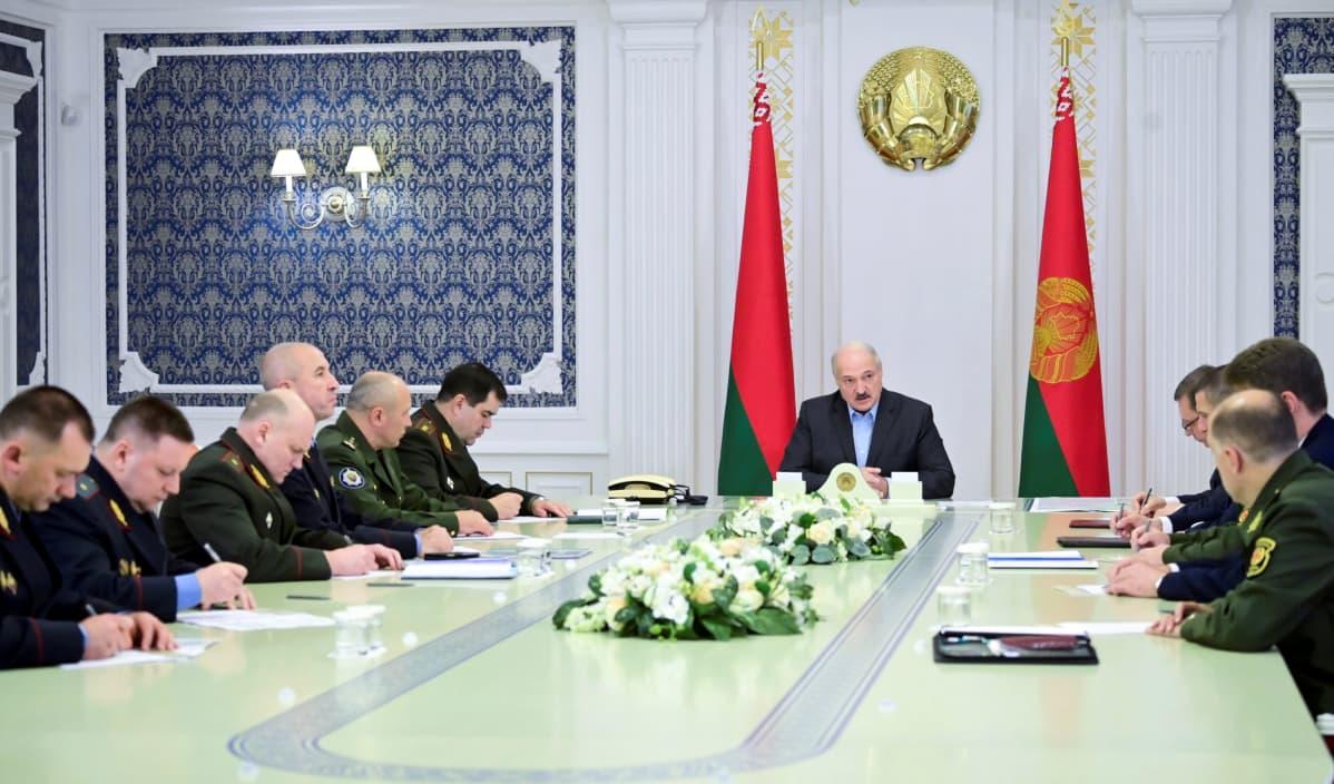 Lukašenka istuu pitkän pöydän päässä tummassa puvussa ilman kravattia. Pöydän sivuilla istuu miehiä univormuissa.