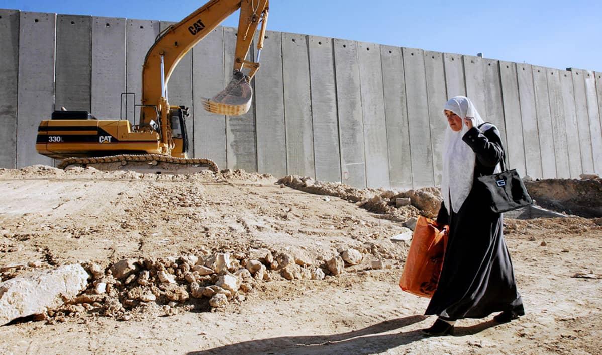 Palestiinalainen nainen kävelee israelilaisten rakentaman muurin vierustalla Itä-Jerusalemissa.