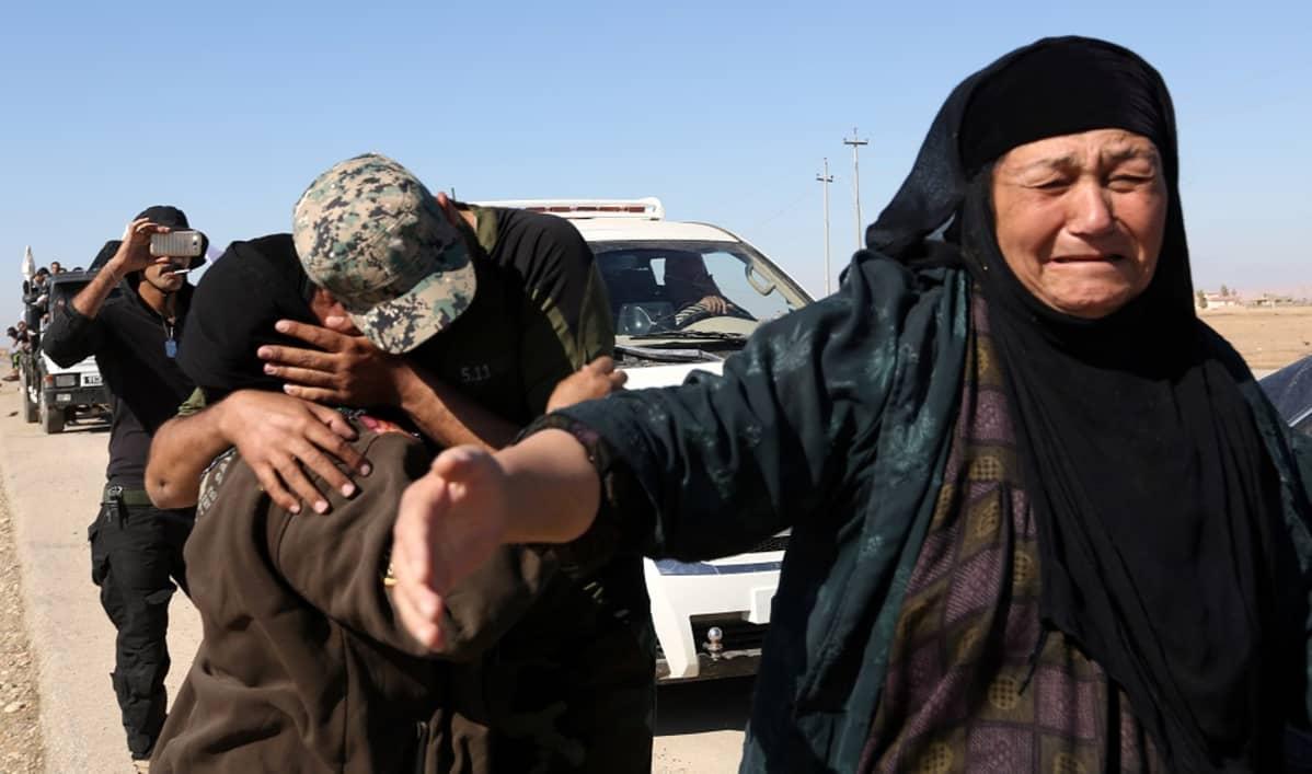 Sotilas halaa tiukasti äitiään. Eedssä itkevä nainen levittää käsiään.
