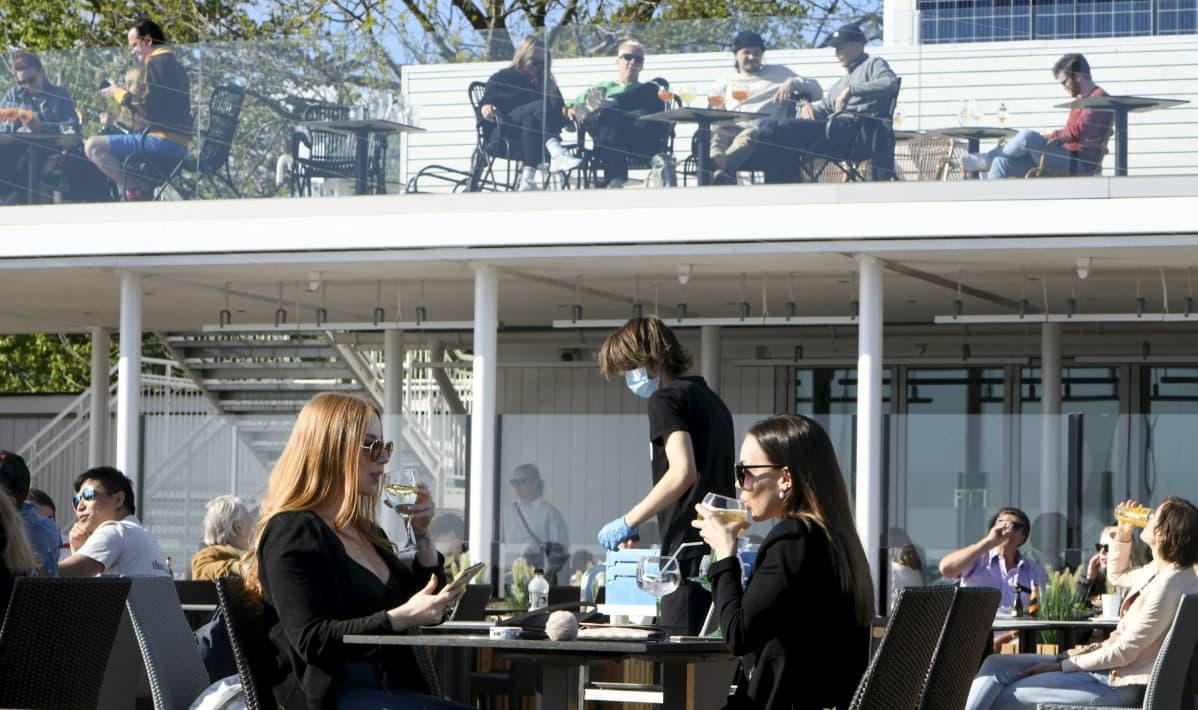 Asiakkaita Cafe Caruselin terassilla aurinkoisella säällä Helsingin Kaivopuistossa.
