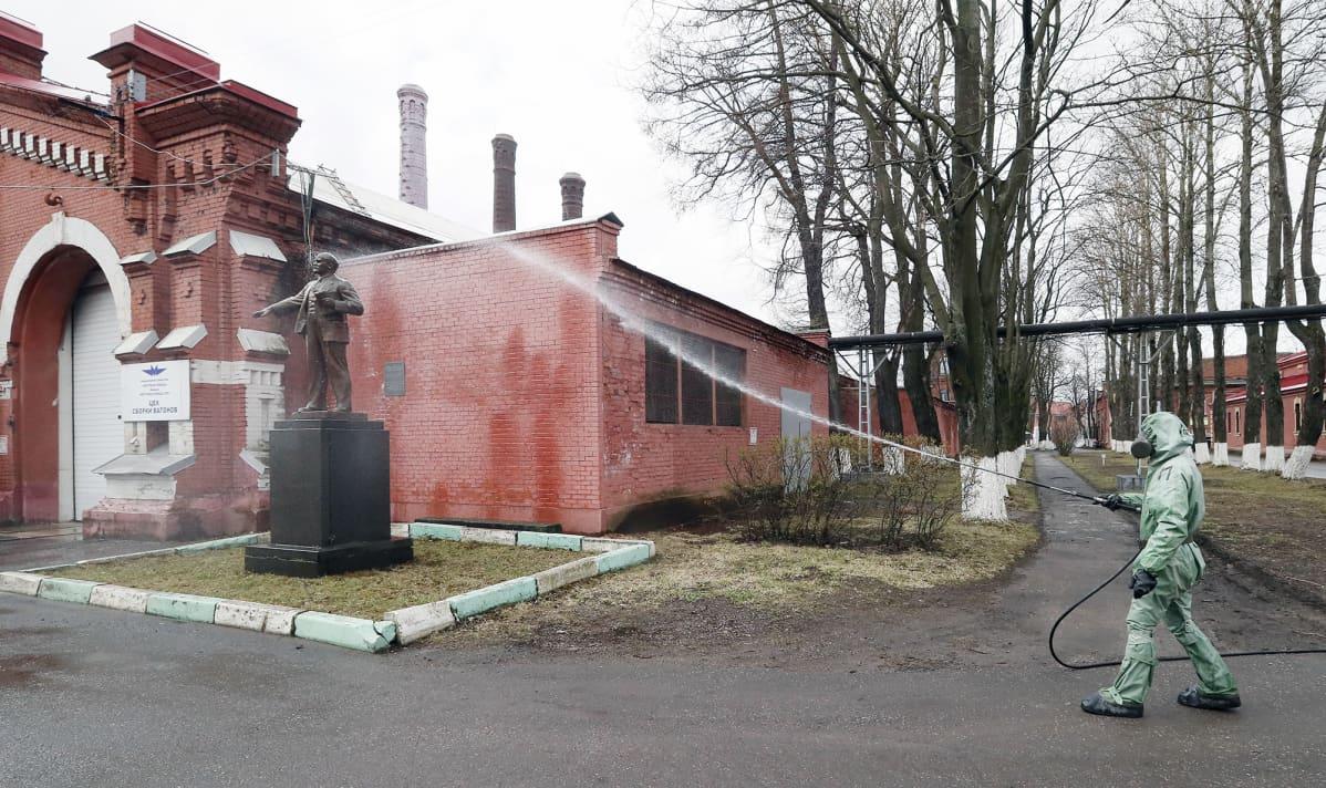Suojavarusteisiin pukeutunut sotilas desinfioi rakennusta ja patsasta Pietarisa.