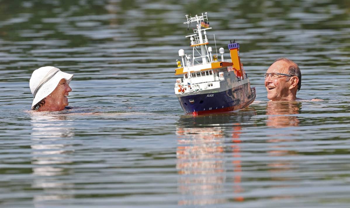 Pariskunta ja pienoisvene järvessä.