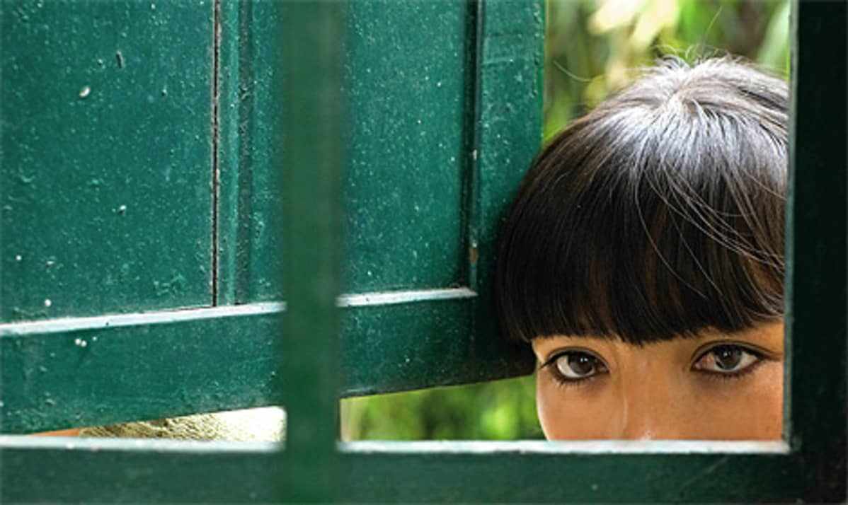 Surusilmäinen nuori nainen katsoo sisään ikkunasta.