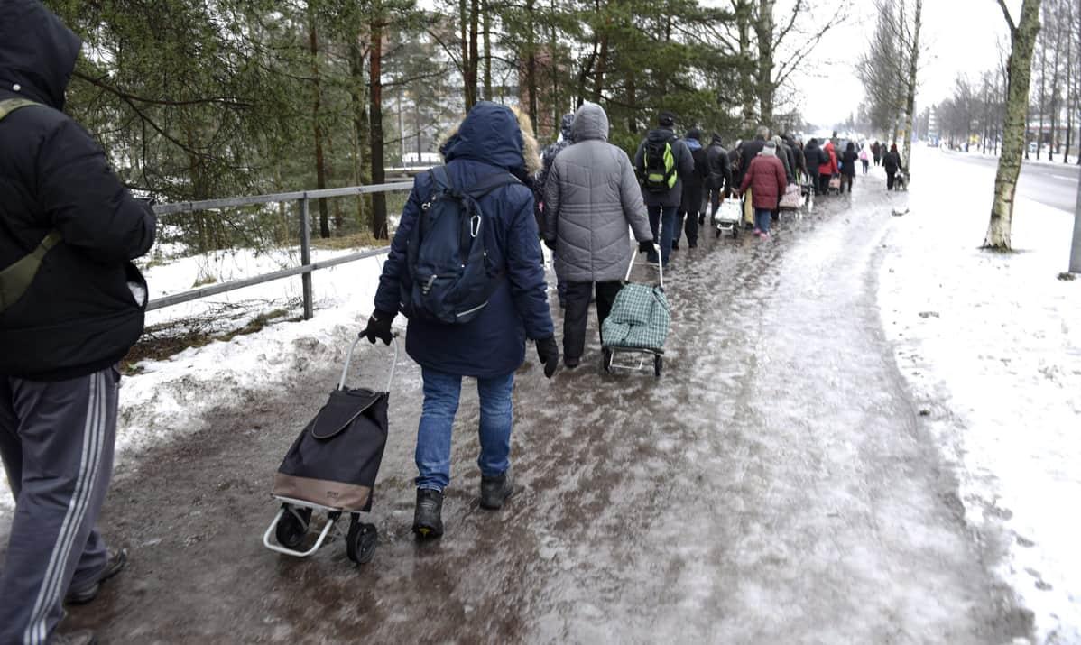 Ihmiset jonottivat elintarvikkeita jäisellä tiellä Helsingin Myllypurossa.
