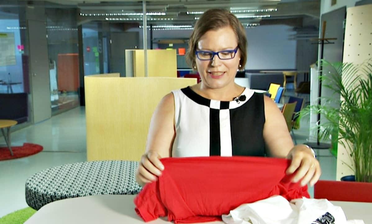 Kirsi Niinimäki tunnustelee vaatteita.