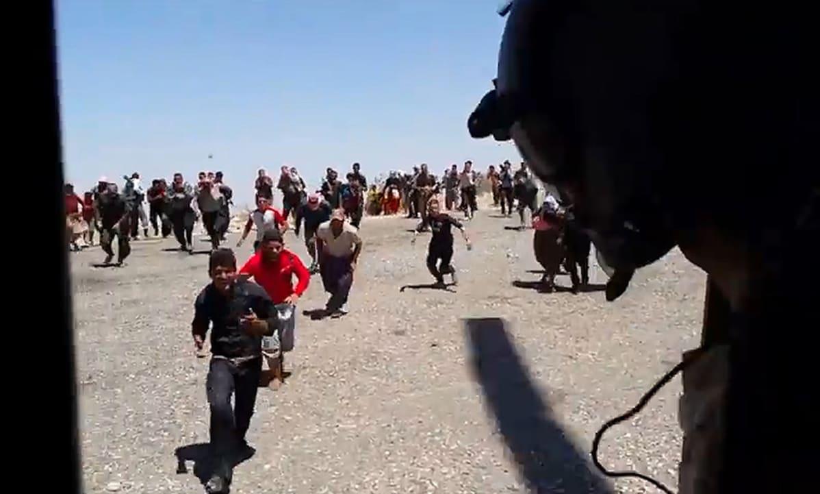 Jesidivähemmistöön kuuluvat ihmiset pakenevat Isis-taistelijoita avustushelikopteriin Pohjois-Irakissa 10. elokuuta 2014.