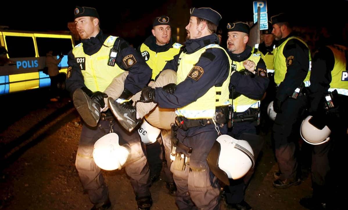 Poliisit häätävät maahanmuuttajia laittomasta leiristä Malmössä.