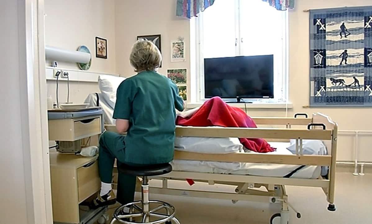 Hoitaja palvelutalon asukkaan vuoteen vieressä.