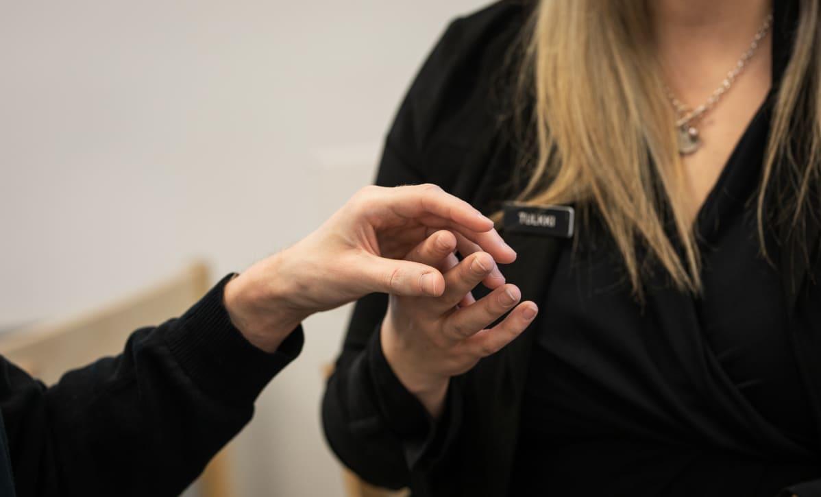Kuulonäkövammainen keskustelee taktiileilla tulkin kanssa
