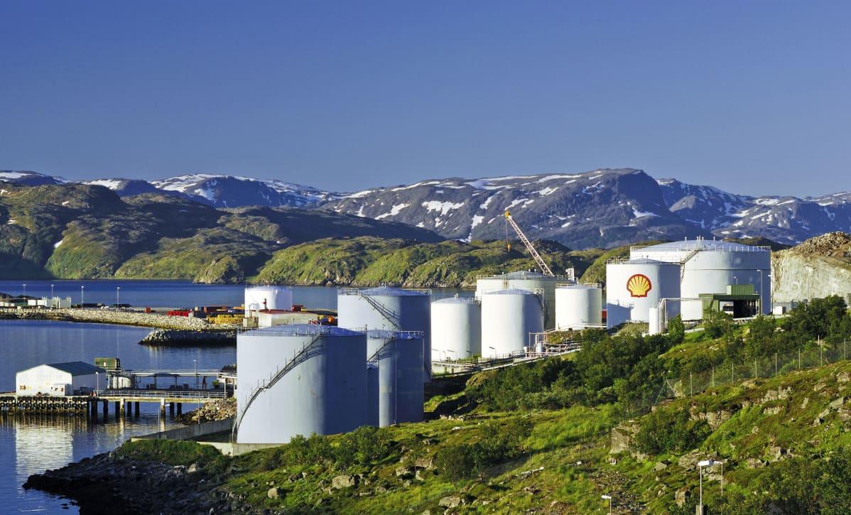 Öljysäiliöitä. Taustalla vettä ja lumisia vuoria.