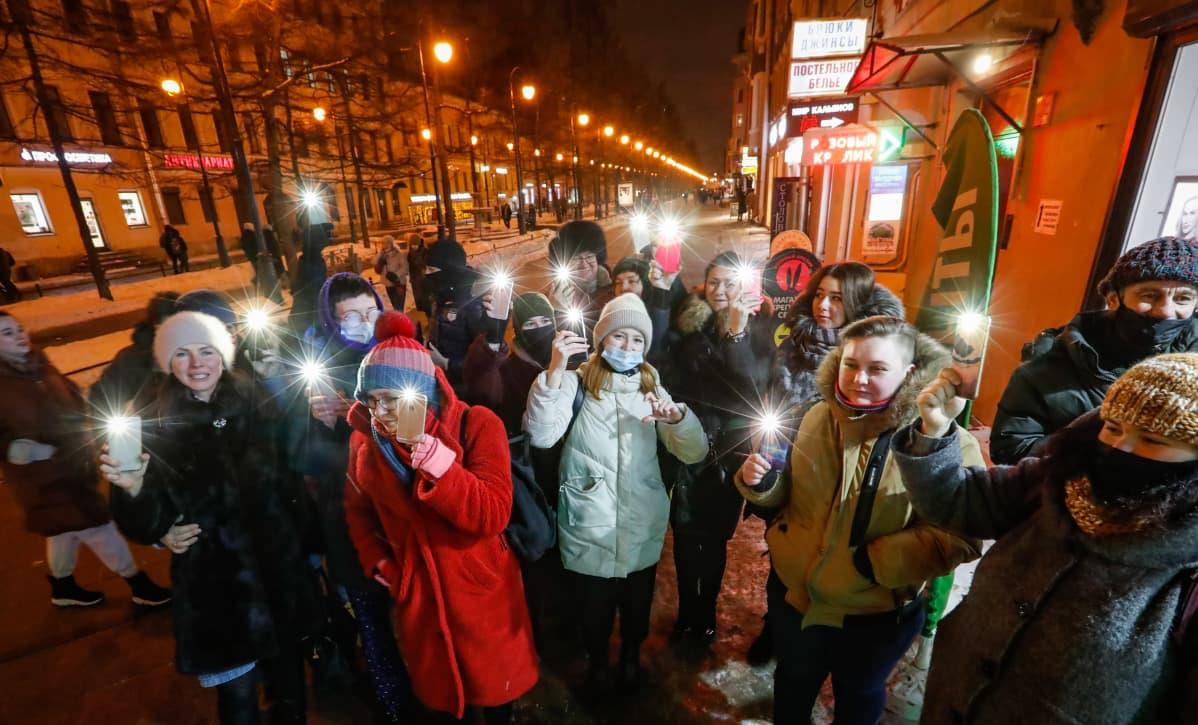 Joukko nuoria ihmisiä seisoo talvisella kadulla Pietarissa pidellen kännyköitään ylhäällä taskulamput sytytettyinä. Monilla on kasvoillaan maskit mutta ei kaikilla.